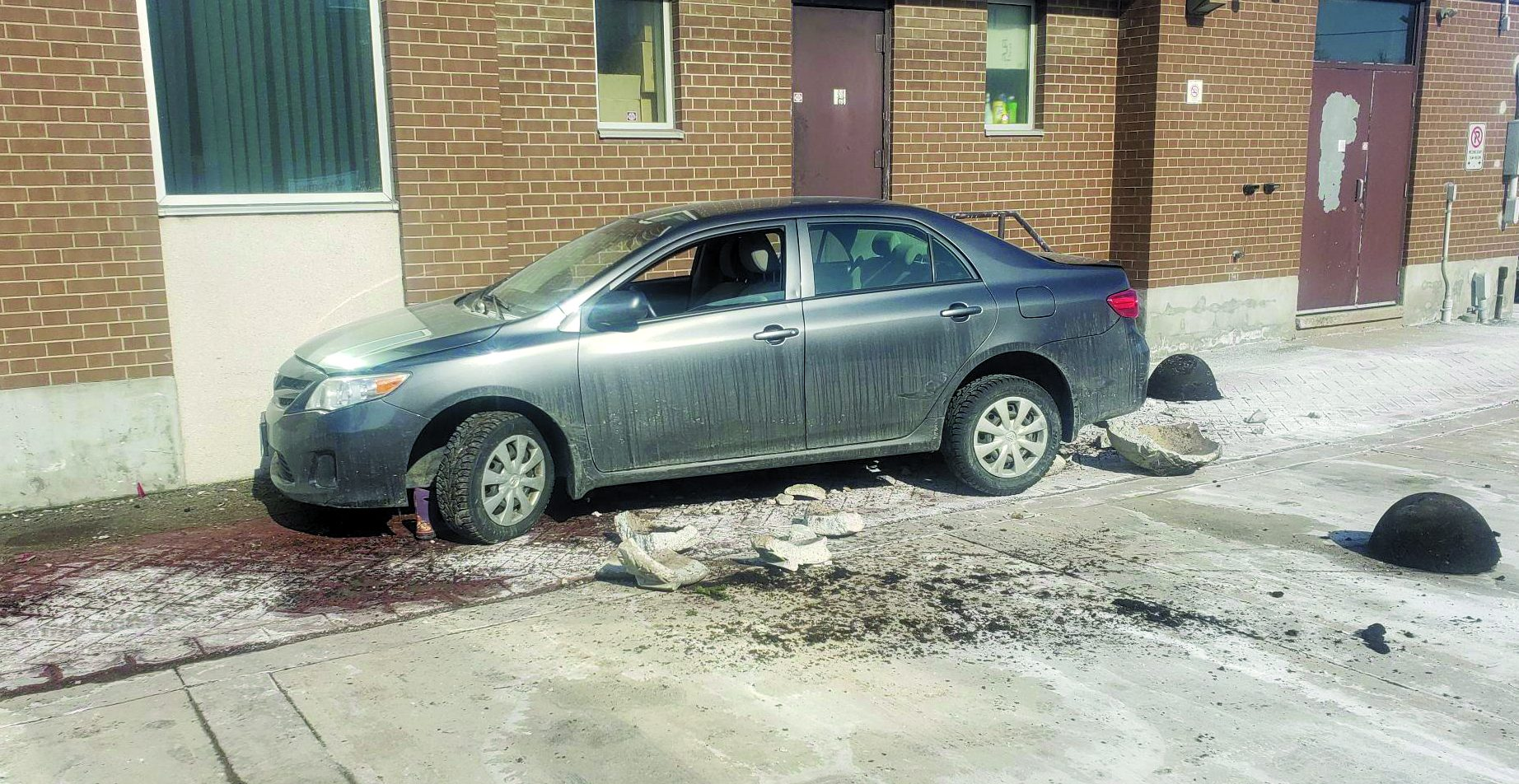Car at edge of building with broken cement flower planters behind it and child's boot in wheel well