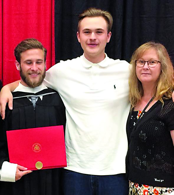 Two young men with their mother at graduation ceremony