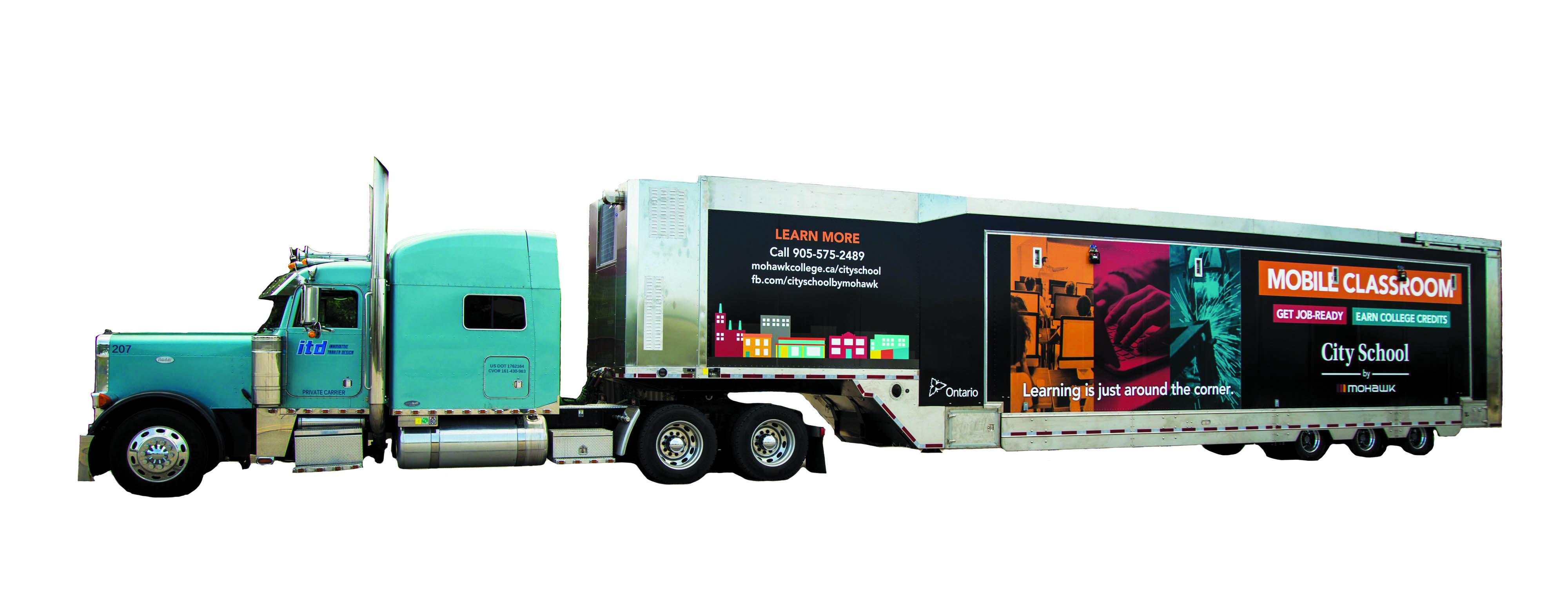 Transport truck pulling portable classroom.