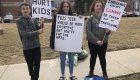 Three students stand together protesting outside high school.