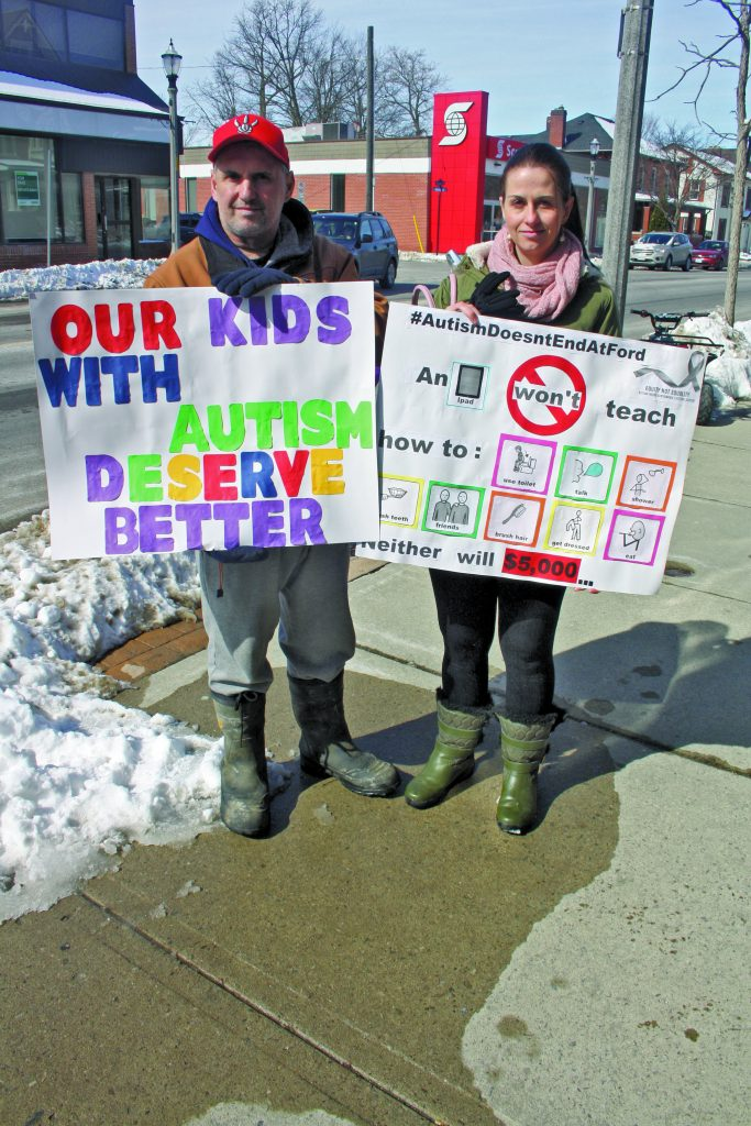 Couple holds sign protesting autism funding