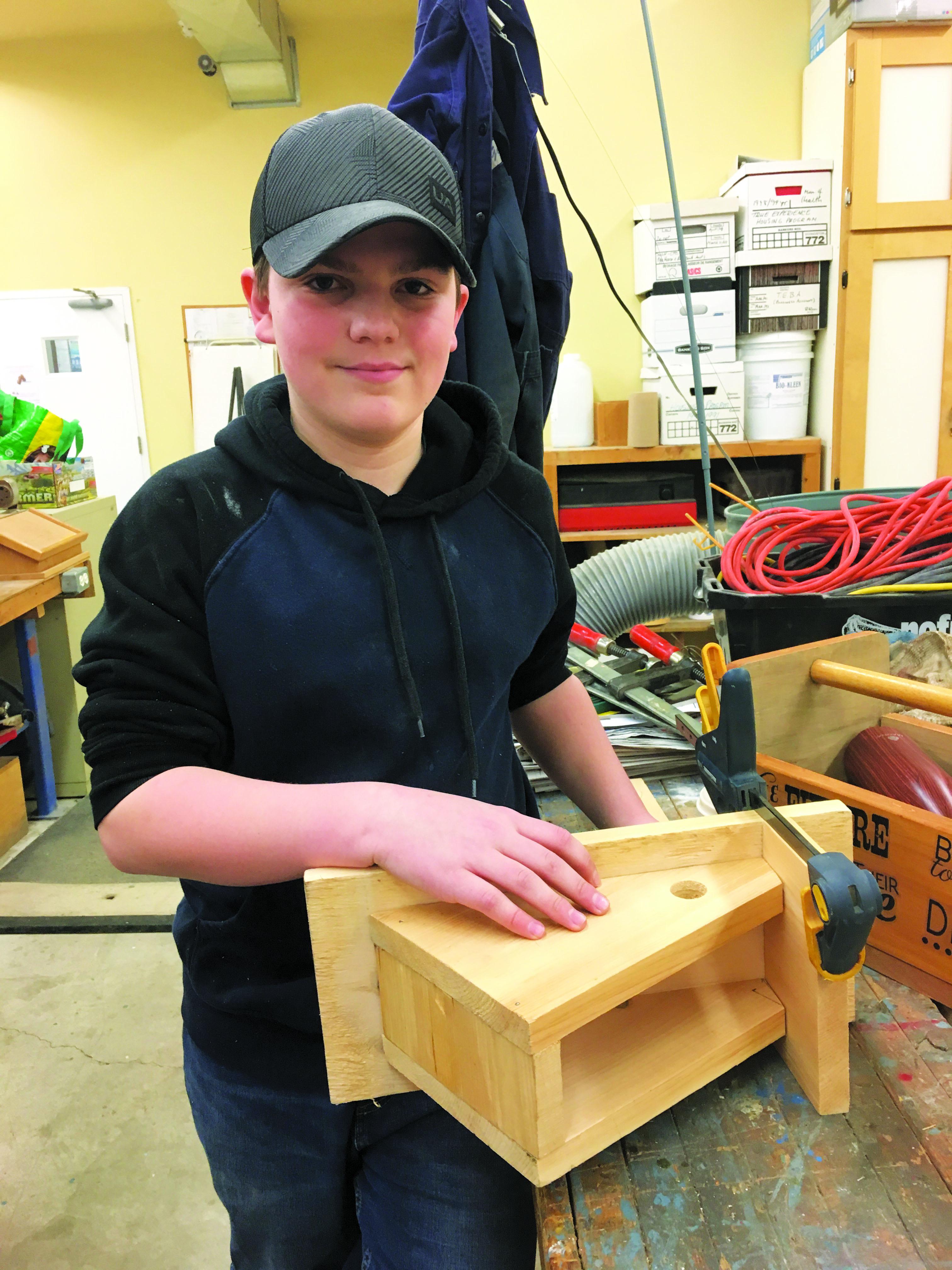 Boy with partially-built bird feeder.
