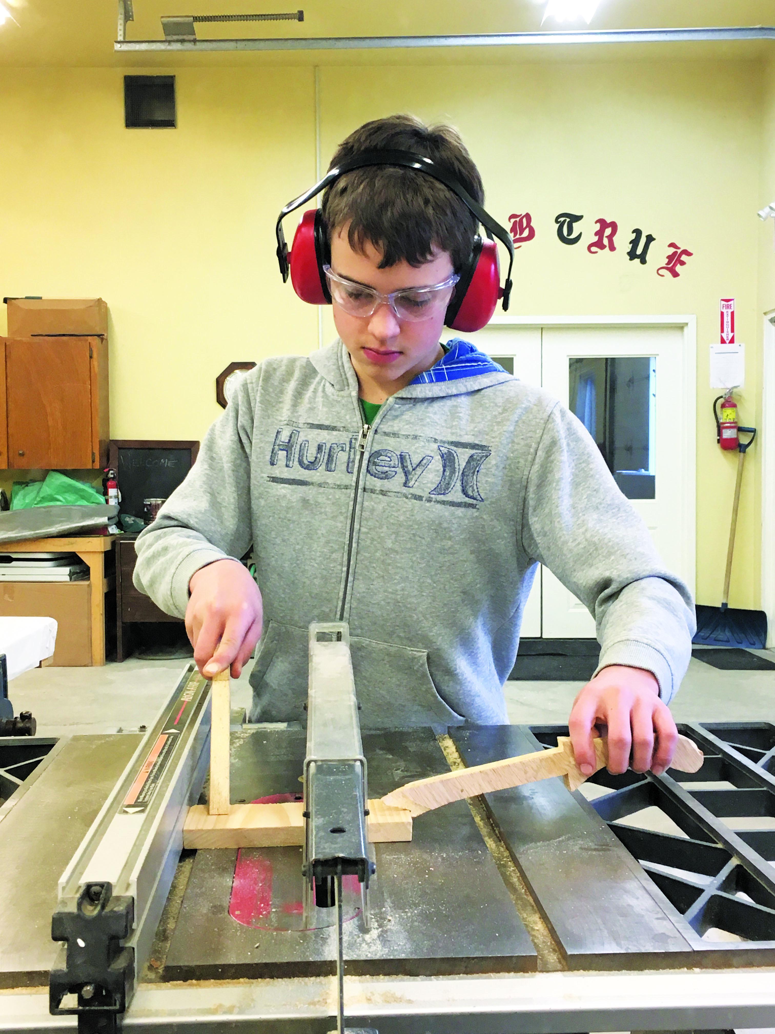 Boy using saw.