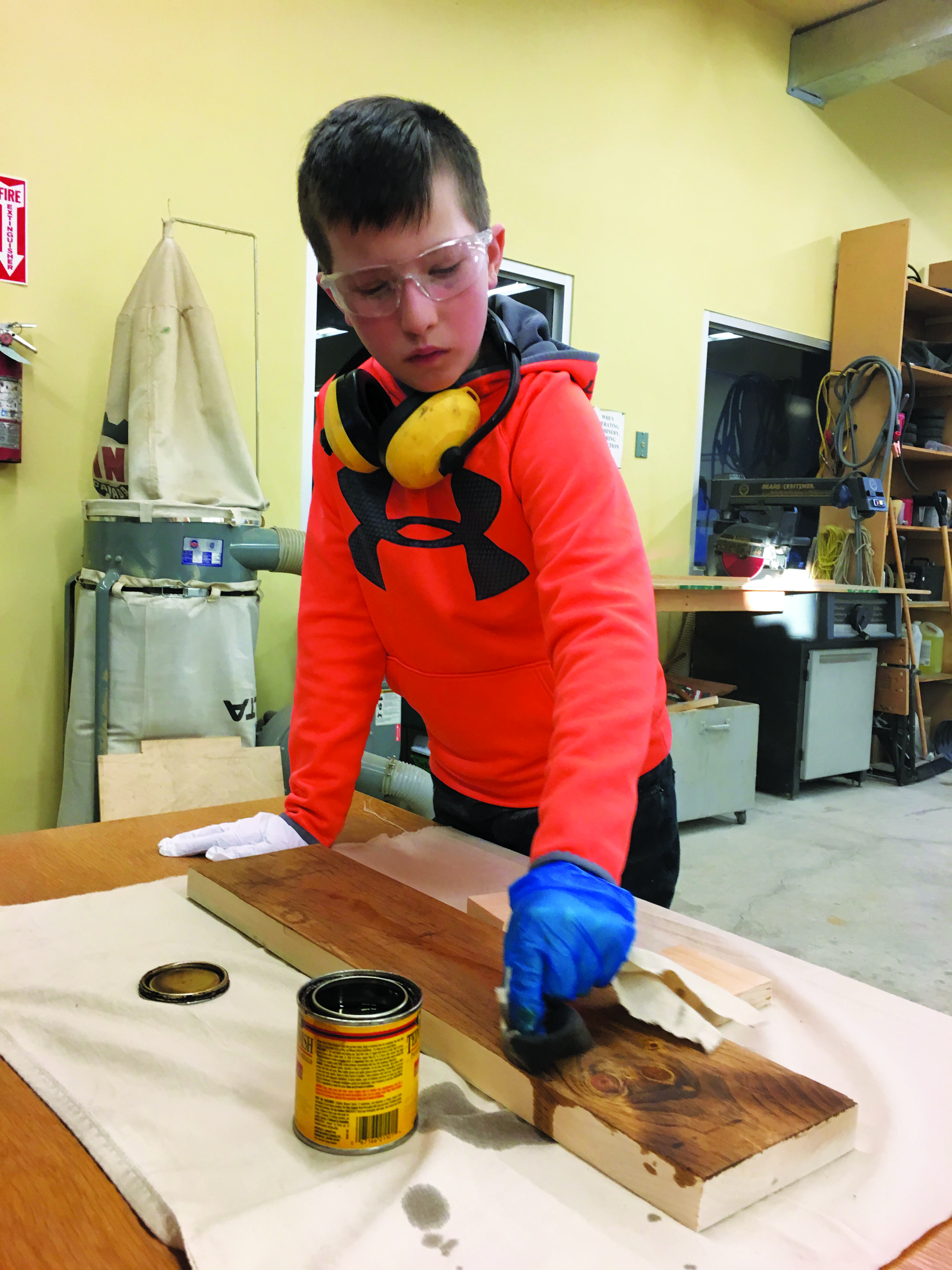 Boy staining plank of wood.