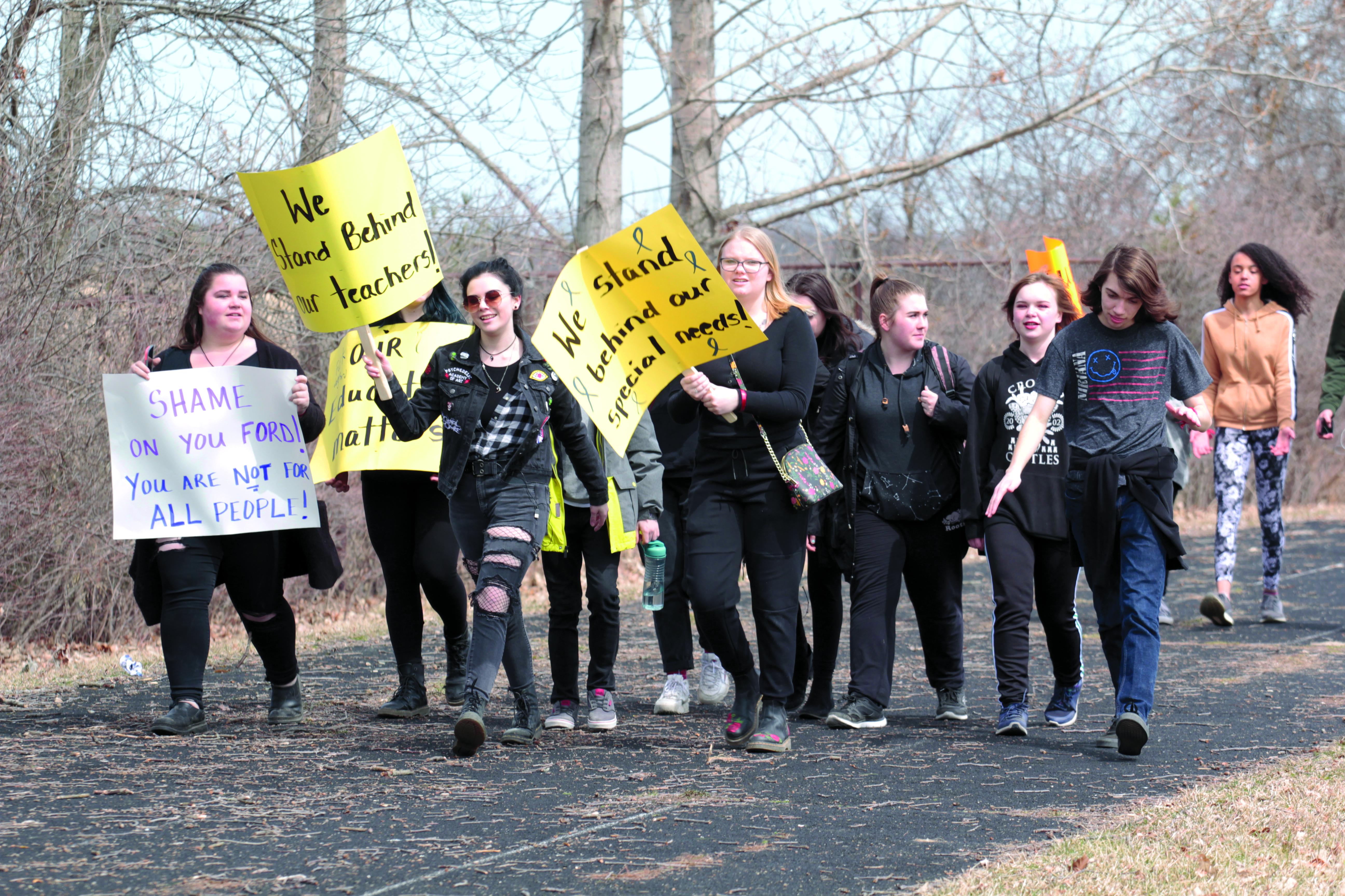 Students march around school track with signs