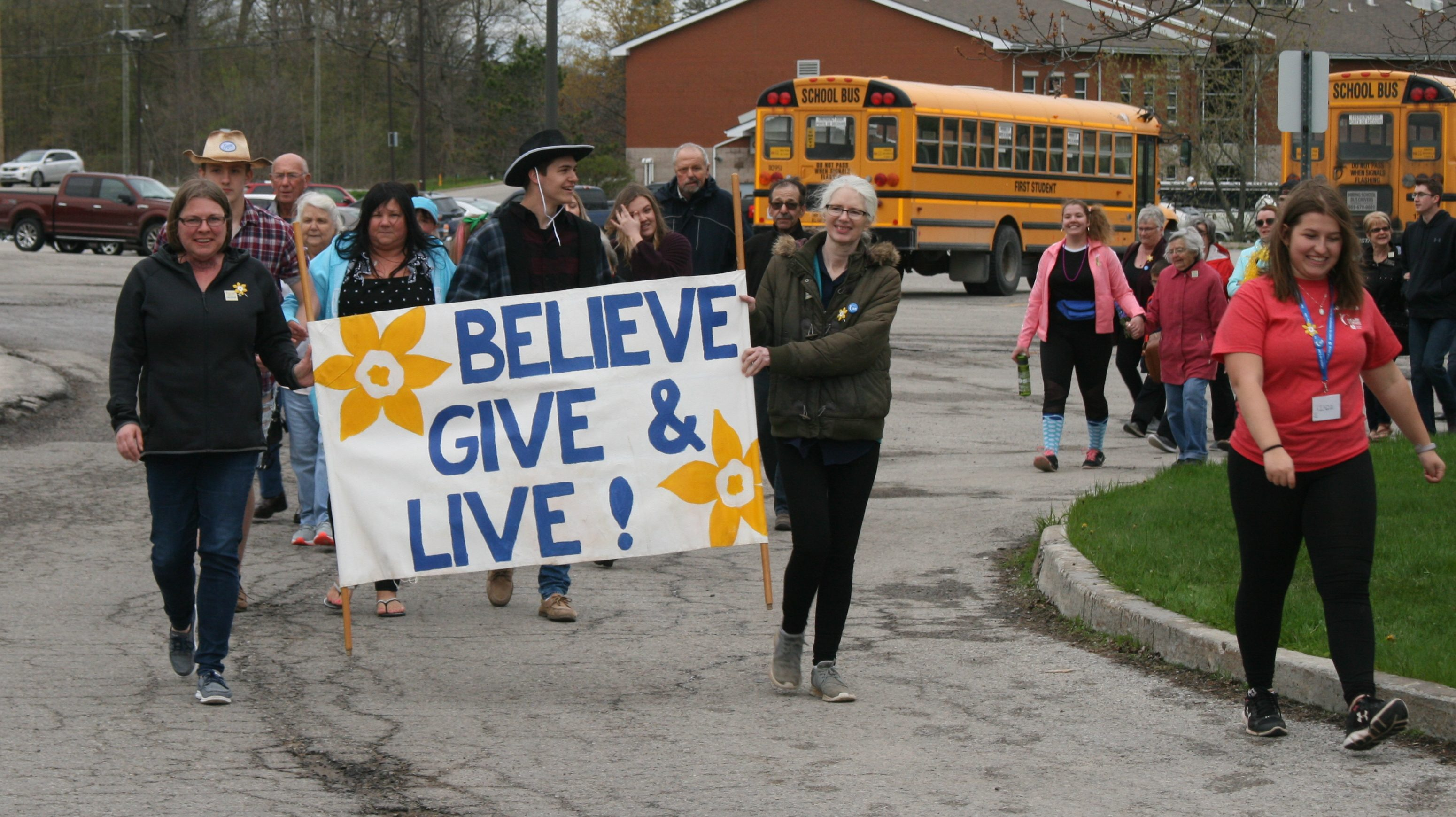 "Group of people walking with sign that says ""Believe, Give, & Live"""